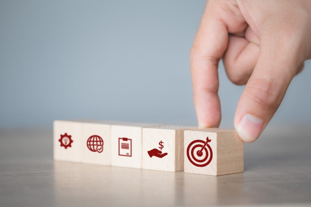 hand-arranging-wood-block-stacking-with-icon-arrow-and-business-targeting-the-business-concept_34936-2804
